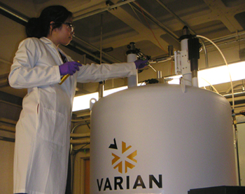 Researcher placing an NMR sample into the 600 MHz VNMRS NMR spectrometer at the UC Davis NMR Facility